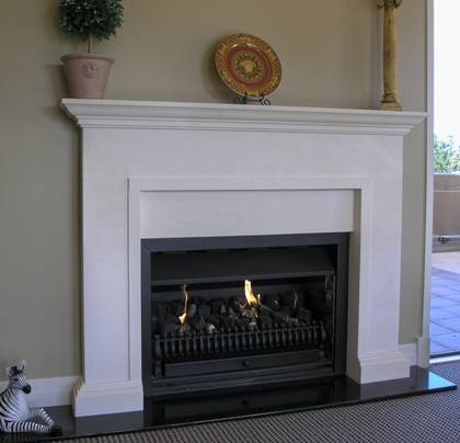Classical surround  and carved mantle in Oamaru Limestone, hearth in Bluestone