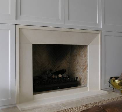 Bevel fireplace with small border style fire surround carved in Oamaru Limestone