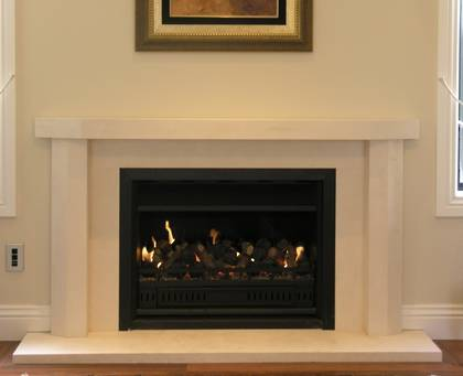 Contemporary fire surround with bevel to outer edge of mantle and jambs, carved in Portuguese Limestone