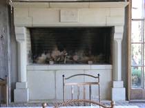 Large Gothique Loggia fireplace with raised firebox carved in Hinuera Stone